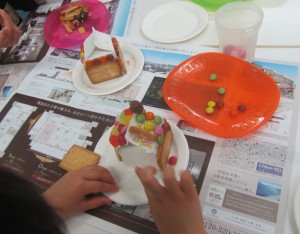 ビスケットの土台に小麦粉の糊をぬってお菓子でデコレーション。素敵なお菓子の家ができました!