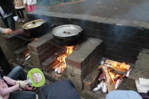 新聞紙とアルミホイルで包んださつま芋も、お鍋と一緒に火にくべて...